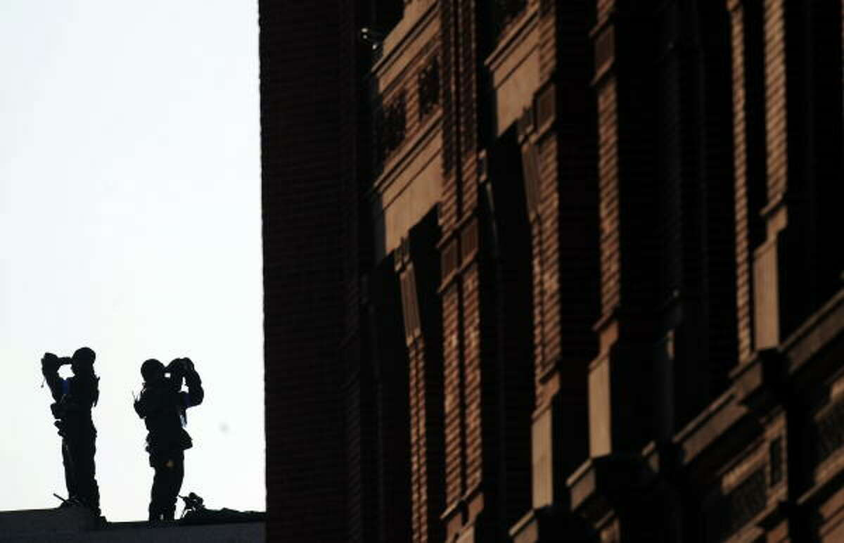 U.S. Secret Service agents scan the area from a rooftop as President Barack Obama takes part in the parade after he was sworn in as the 44th U.S. President in Washington.