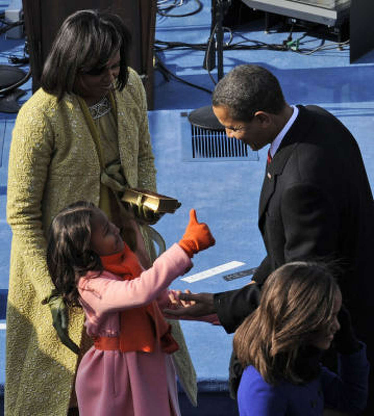 Sasha gives her father, President Barack Obama, the thumbs up after he took the oath of office. The girls have moved into the White House and are preparing for their new life.