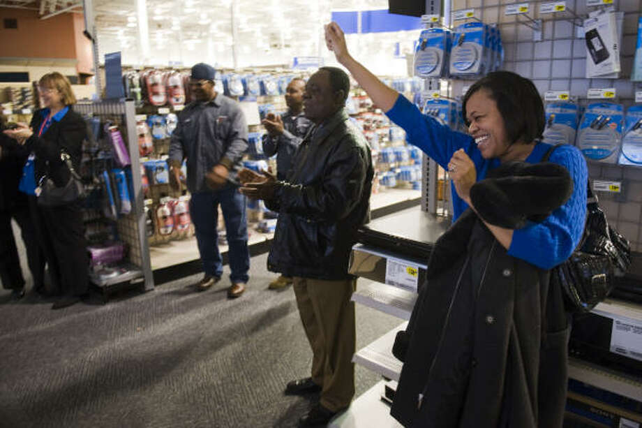 Norma Jarrett-York, right,  celebrates at the end of the oath of office as a small crowd gathers around a television screen at the Best Buy store near the Galleria to watch the historic swearing-in of President Barack Obama on Tuesday. Photo: Smiley N. Pool, Houston Chronicle