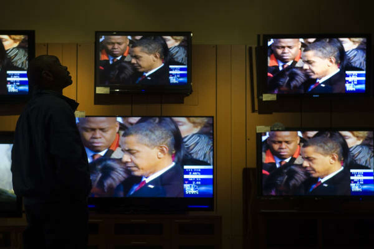 Nelson Coleman of Houston watches coverage of the inauguration of President Barack Obama at the Best Buy store near the Galleria on Tuesday.