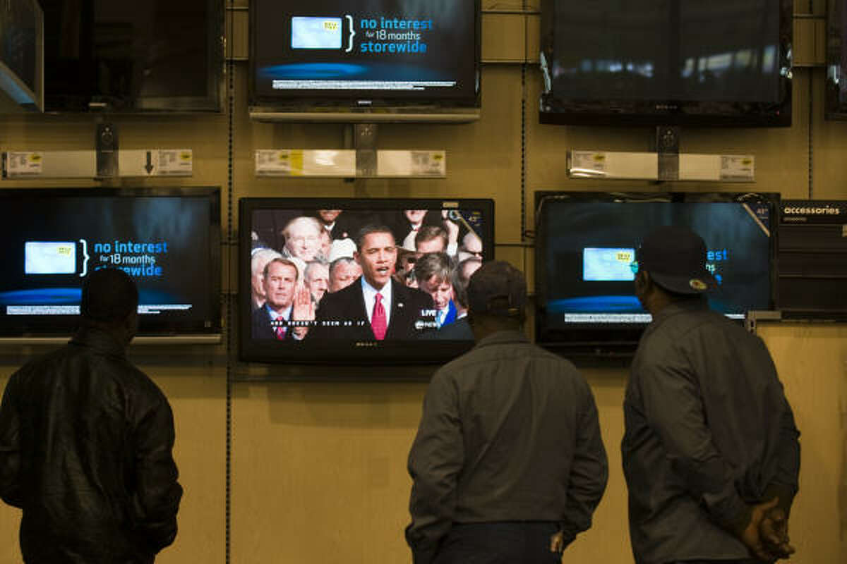 A small crowd gathers around a television screen at the Best Buy store near the Galleria to watch the historic swearing-in of President Barack Obama on Tuesday.