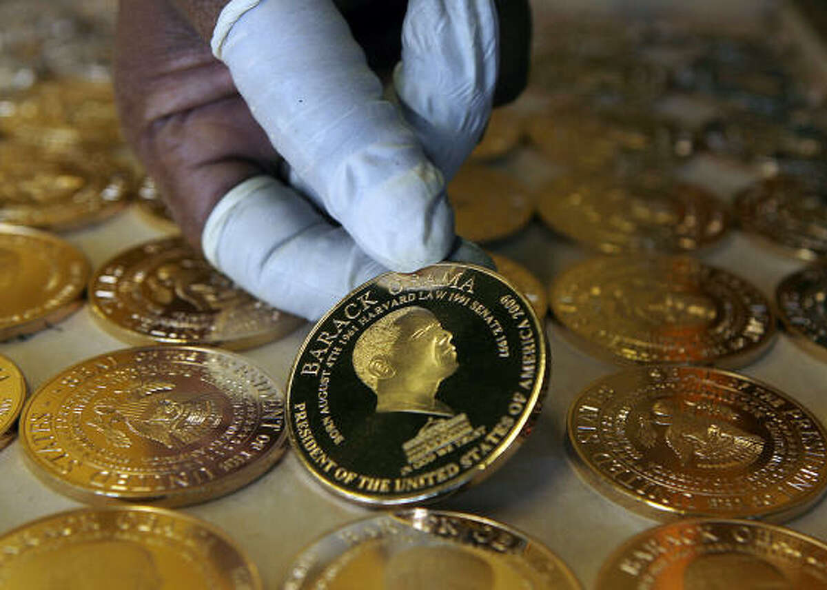 A worker at the Birmingham Mint factory in Birmingham, England, holds a commemorative gold-plated coin worth $20 each Monday. The collectibles were to be shipped to the U.S.