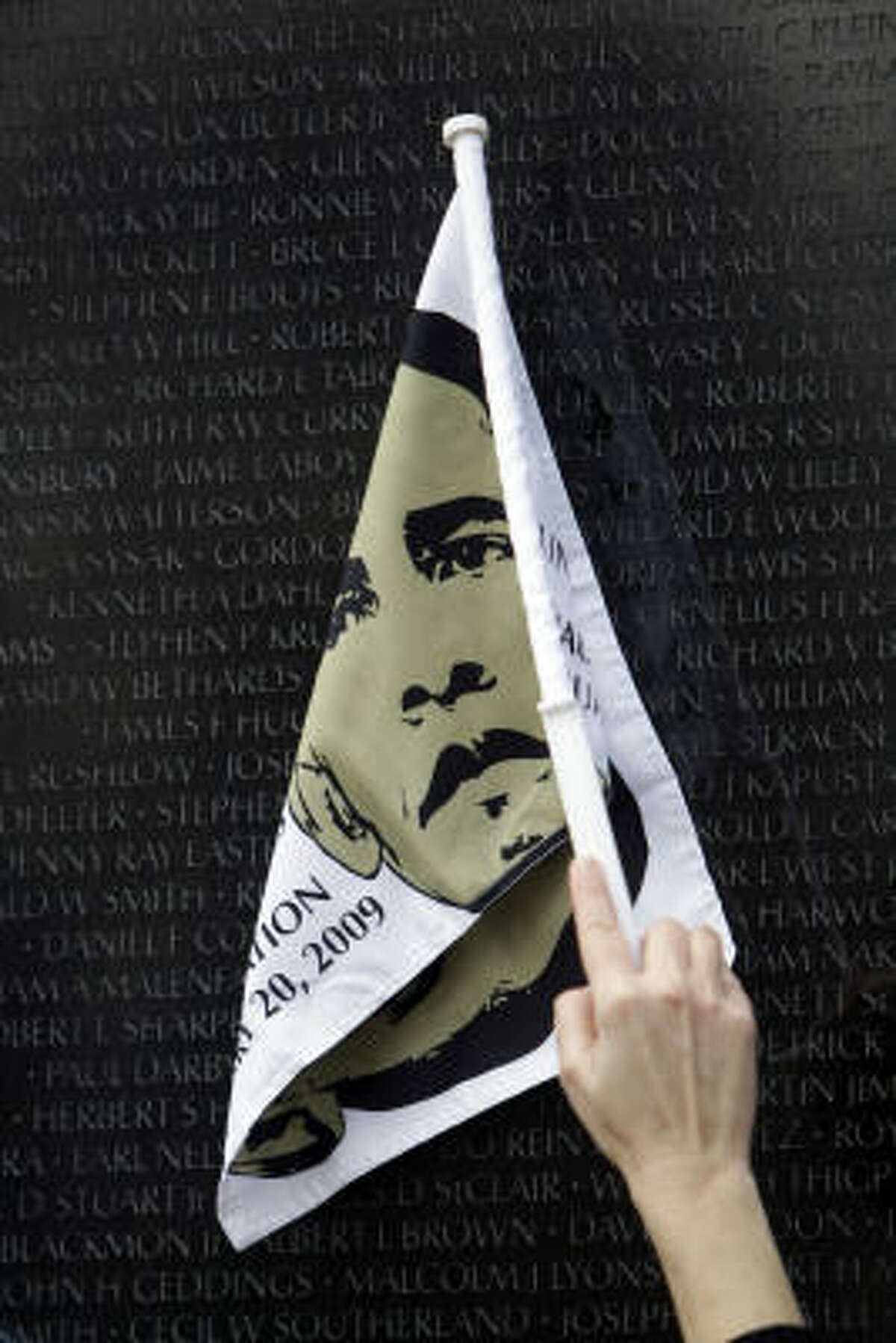 Tour guide Suzanne Fauteux, of Washington, carries a flag with the image of Barack Obama, as she leads a group of students from Lakewood, Calif. through the Vietnam Veterans Memorial in Washington, Monday.
