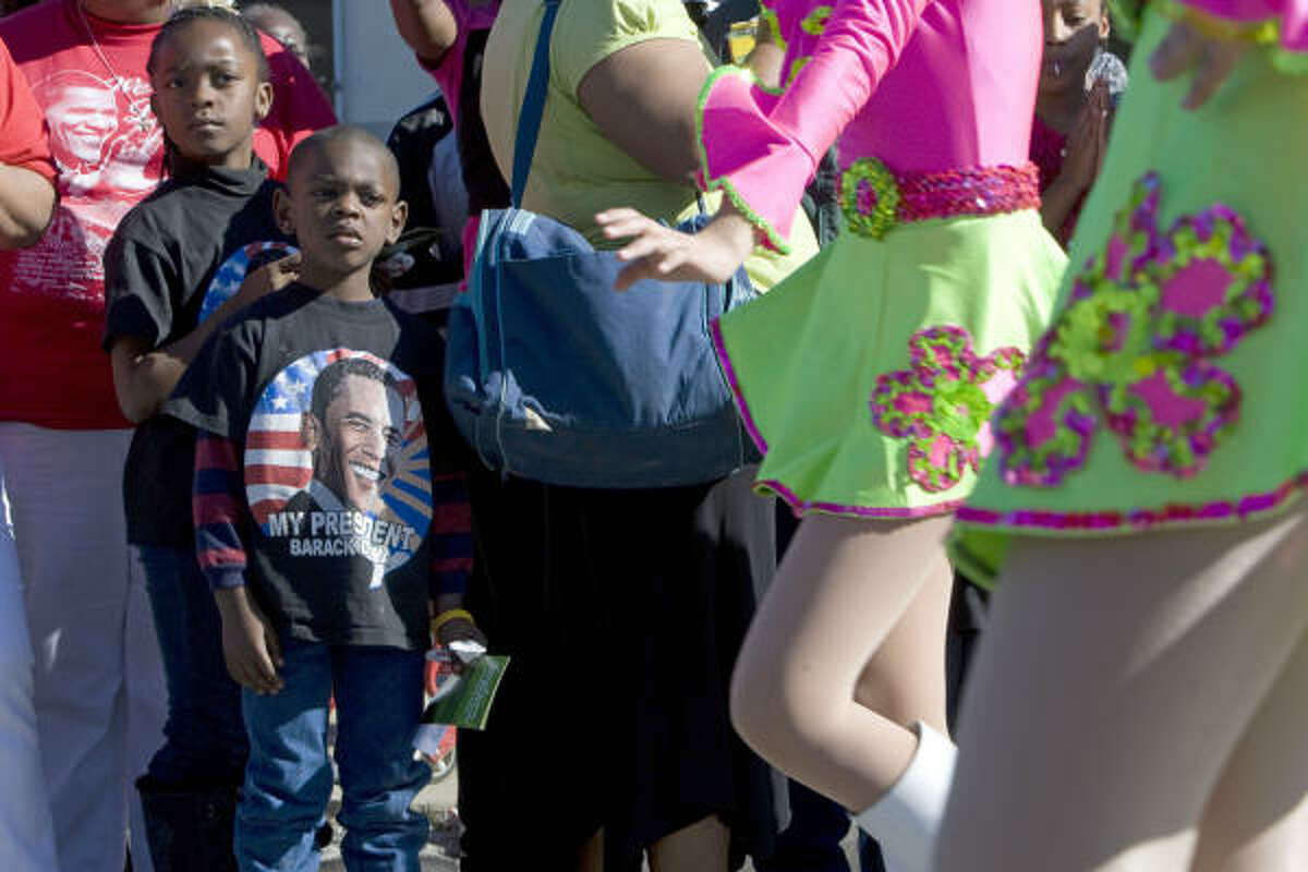 Jalen Harrell, 5, and his sister La'nia Harrell, 8, left, watch cheerleaders pass by during the Black Heritage Society's 31st annual Martin Luther King Jr. Day parade in south Houston along Martin Luther King Jr. Boulevard on Monday.