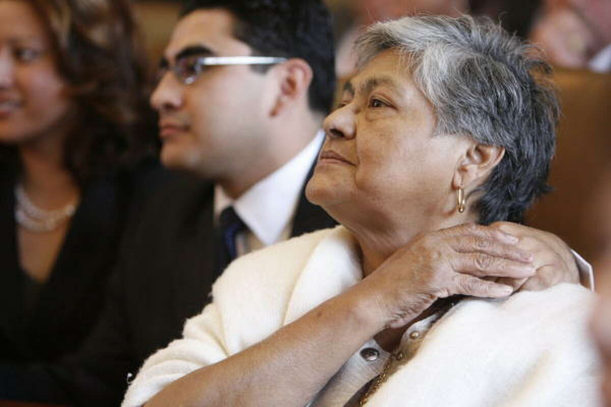 Moments before Armando Walle is sworn in, he holds the hand of his grandmother, Polly Zamarripa.