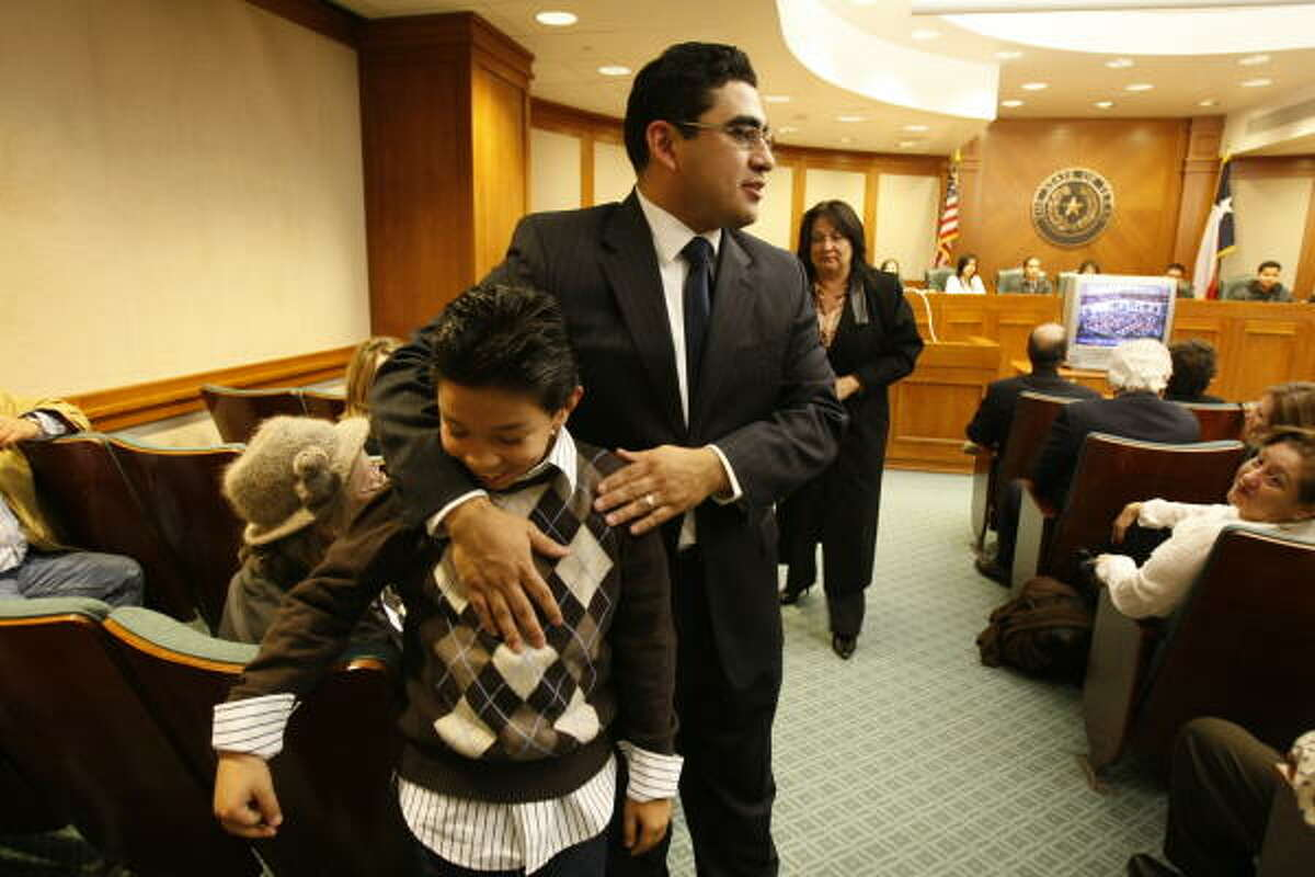 Walle pats young supporter Trey Lopez, who is asking for a note so that he won't get in trouble for missing school.