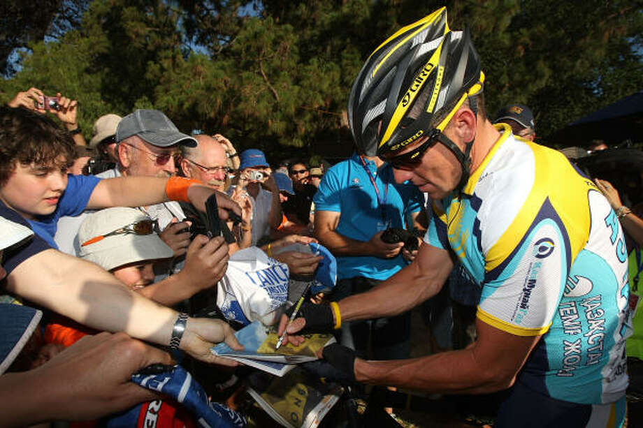 Lance Armstrong signs autographs before the Down Under Classic criterium, held in conjuction with the Tour Down Under which begins on Tuesday. Photo: Ezra Shaw, Getty Images
