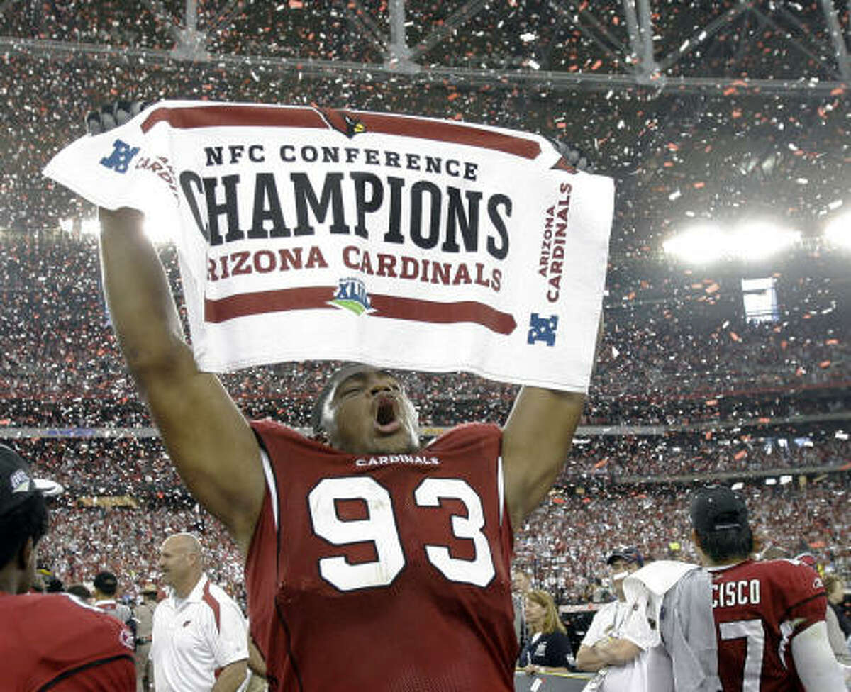 Cardinals defensive end Calais Campbell shows off a banner boasting a feat Arizona has never been able to accomplish: An NFC conference title. They earned a trip to Super Bowl XLIII by beating the Eagles, 32-25.