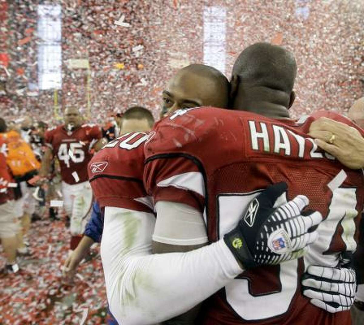 Cardinals cornerback Ralph Brown, left, and linebacker Gerald Hayes embrace during the postgame celebration.
