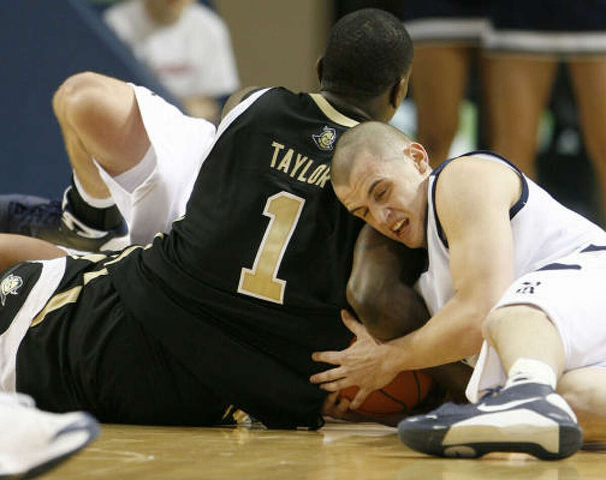 Central Florida 77, Rice 52 Rice guard Cory Pflieger, right, dives to the floor for a loose ball with Central Florida guard Jermaine Taylor during the first half.