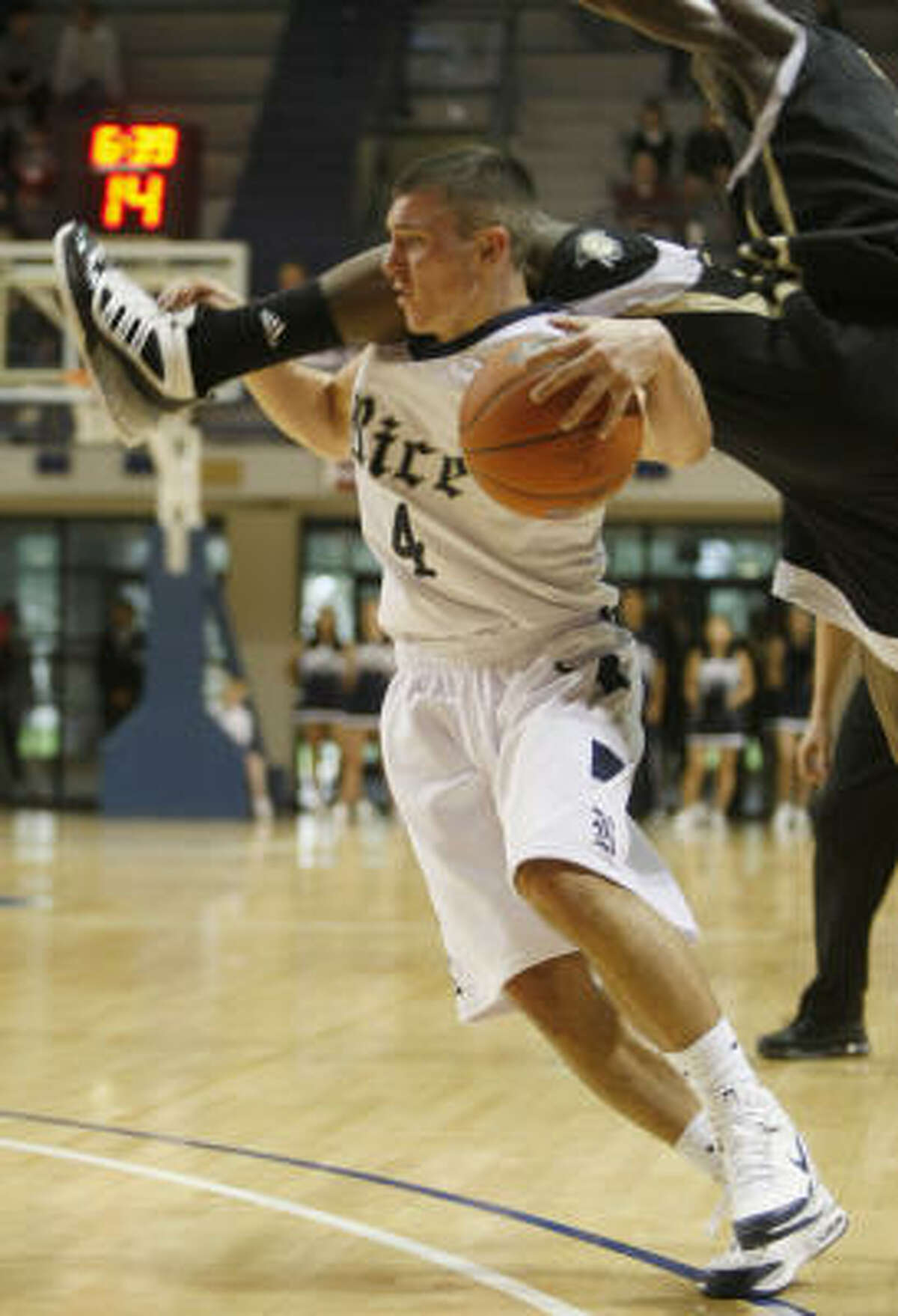Rice guard Connor Frizzelle (4) is fouled by Central Florida guard Jermaine Taylor during the first half.