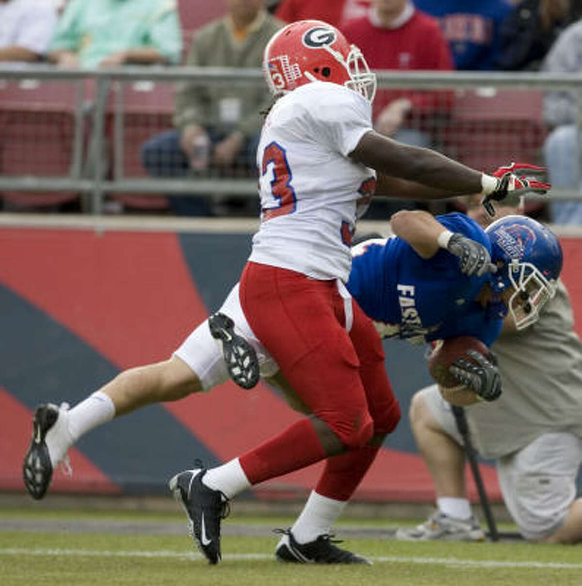 Ian Johnson of Boise State and the West team dives pas Georgia's Dannell Ellerbe.
