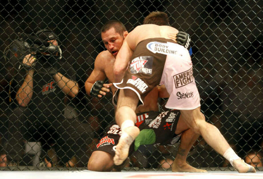 Rich Franklin pins Dan Henderson against the cage and tries to knee him. Photo: Peter Morrison, AP