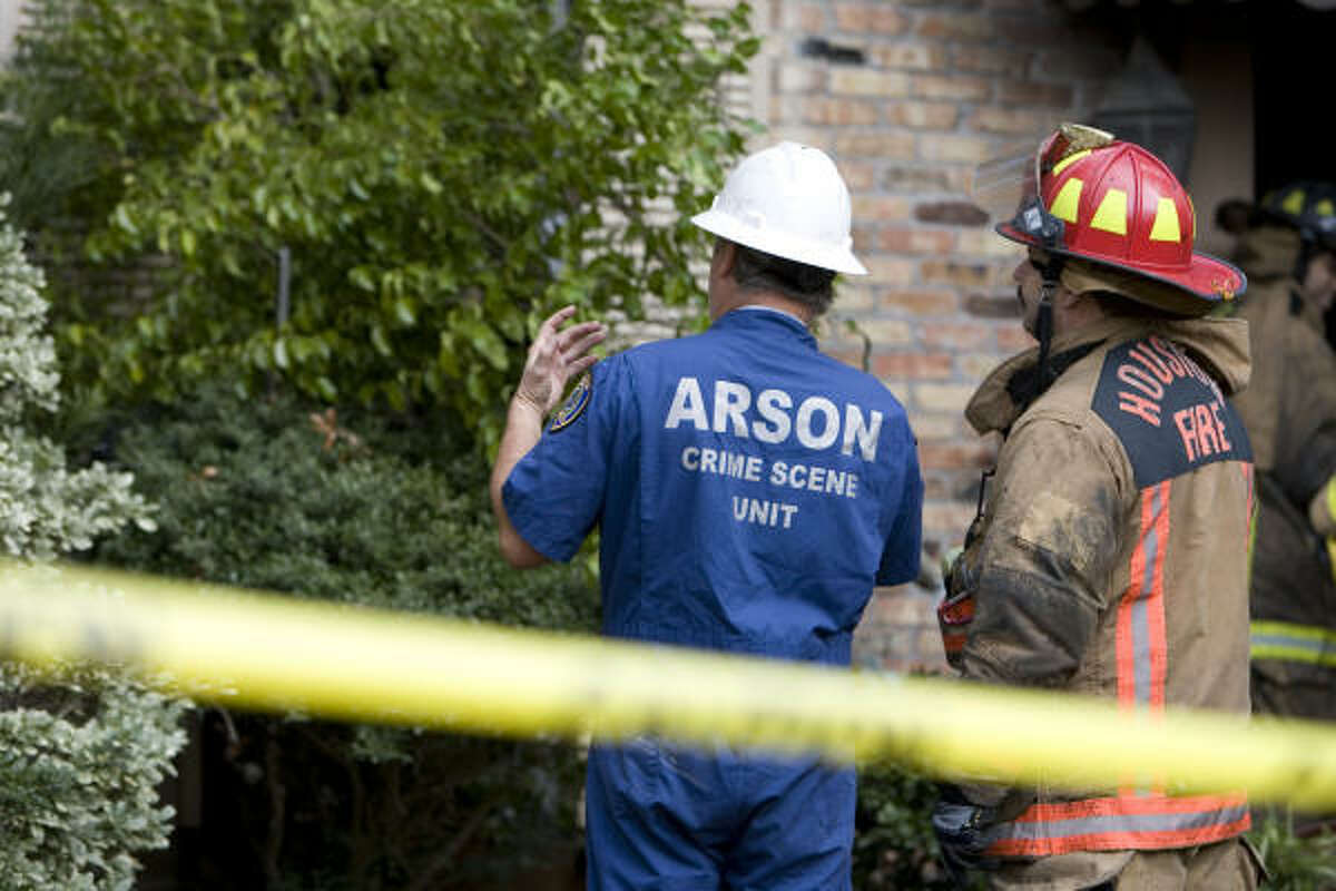 An arson investigator and a Houston firefighter look at the remnants of the fire.