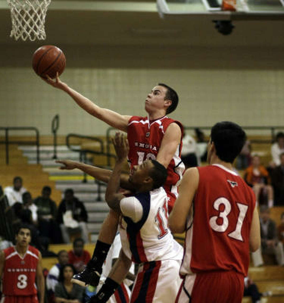 Memorial's Parker Troutner drives to the basket over Alief Taylor's Marquise Wells.