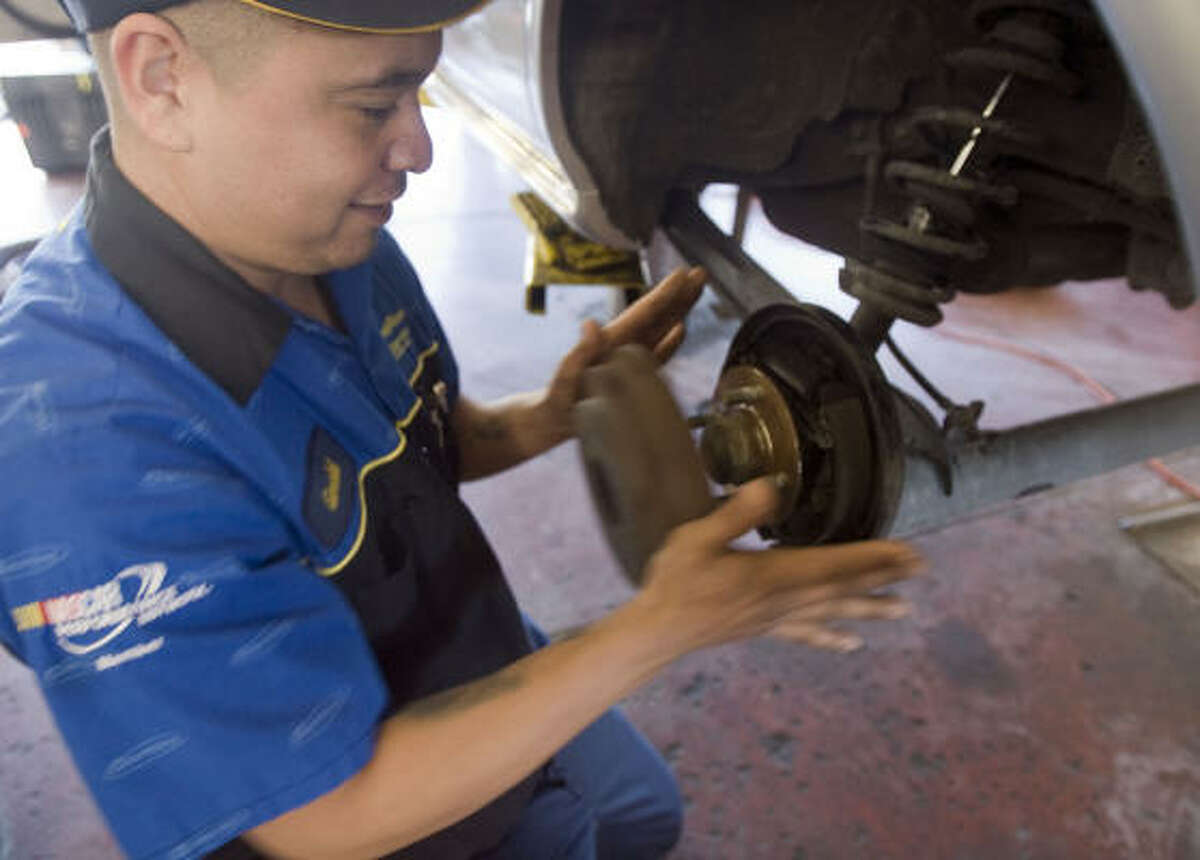 Gerald Sanchez, a technician with Memorial Tire & Auto, removes a rear brake drum from Mike Mertz's car.