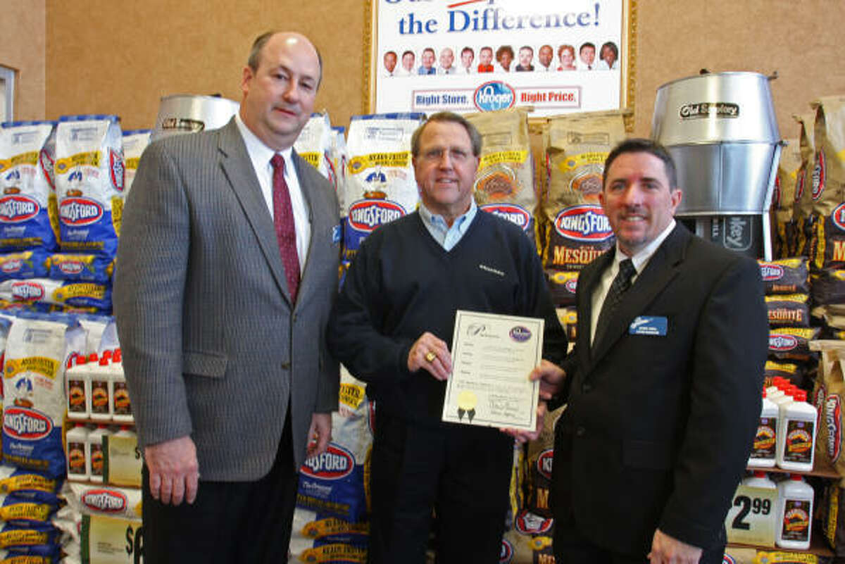 Missouri City Mayor Allen Owen, in the center, holds a proclamation her presented to Chris Hall, Store Manager, on the right. Bill Breetz of Kroger on the left.