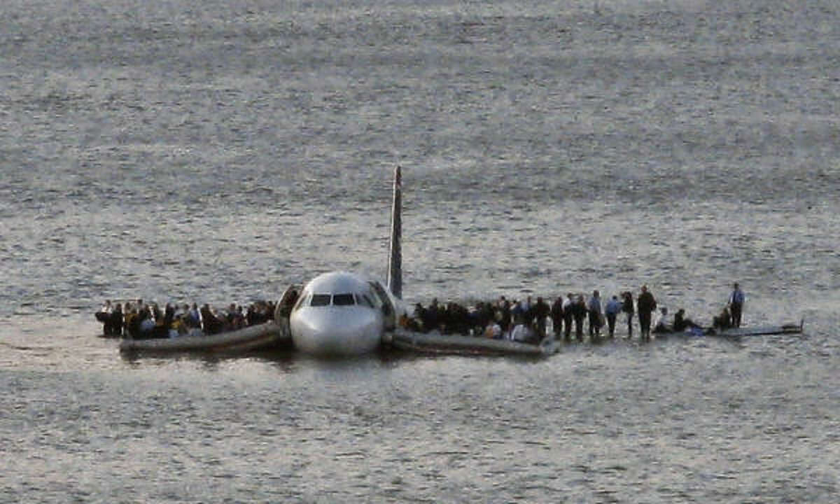 Airline passengers wait to board a ferry to be rescued on the wings of a US Airways Airbus 320 jetliner that safely ditched in the frigid waters of the Hudson River in New York on Thursday.