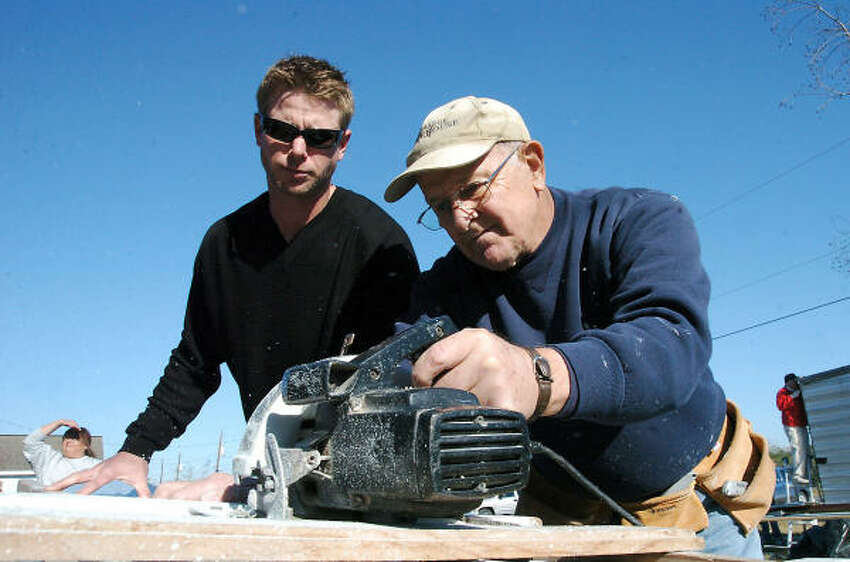 Bay Area Habitat for Humanity volunteer Merle Denny gets a helping hand from Astros pitcher Brandon Backe.