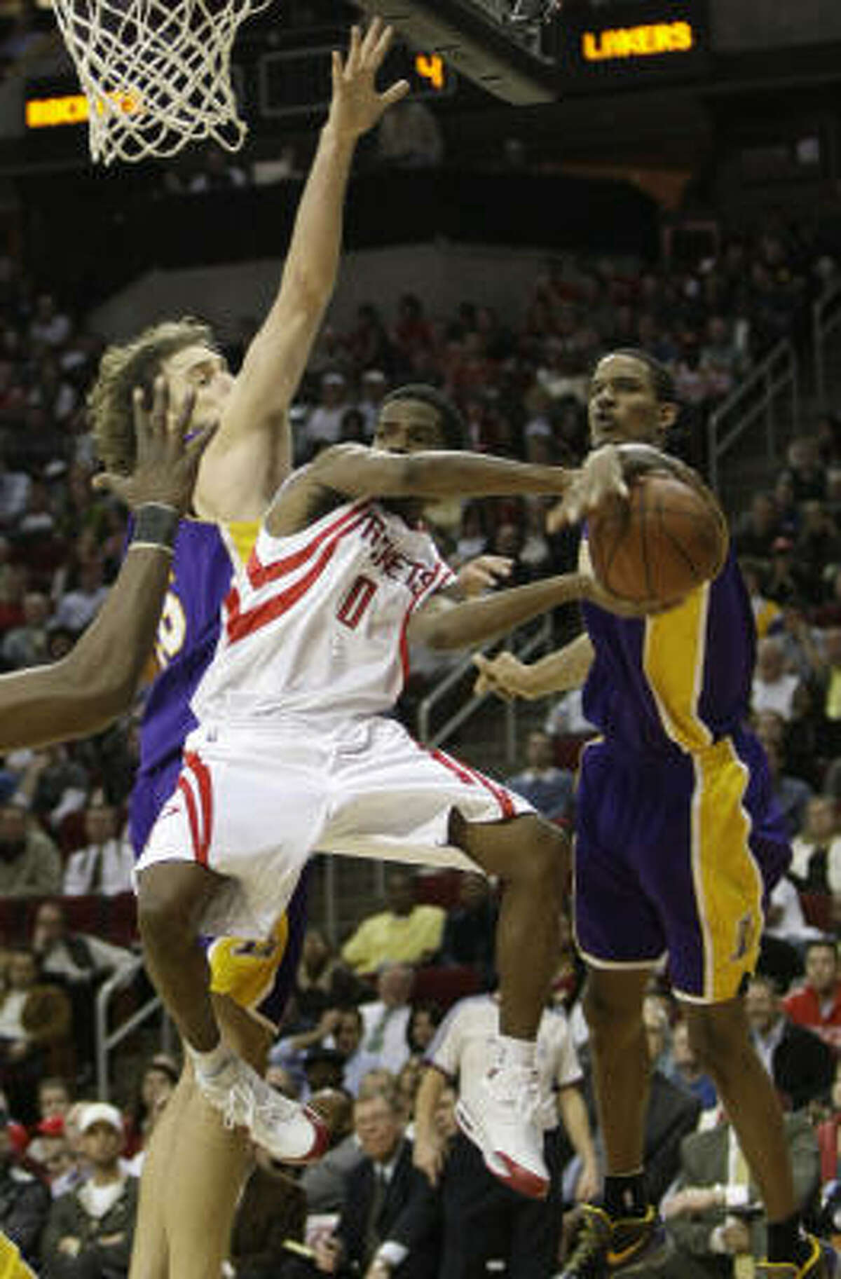Lakers forward Trevor Ariza, right, knocks the ball away from Rockets guard Aaron Brooks as he tries to drive the lane against Lakers forward Pau Gasol in the second half.