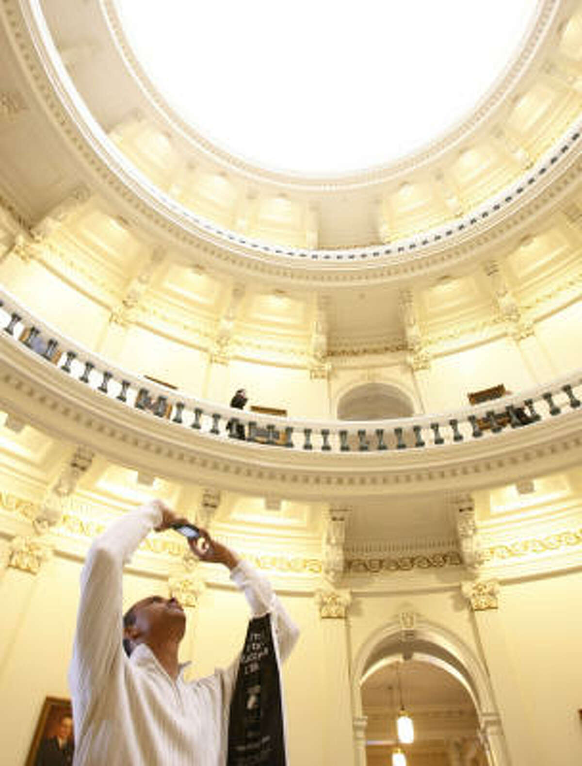 Quincy Thomas, 17, a senior at McArthur High School in Houston, takes a photo of the Texas State Capitol building Tuesday in Austin. Thomas came to see former McArthur student, Armando Walle, be sworn in to the Texas House of Representatives.