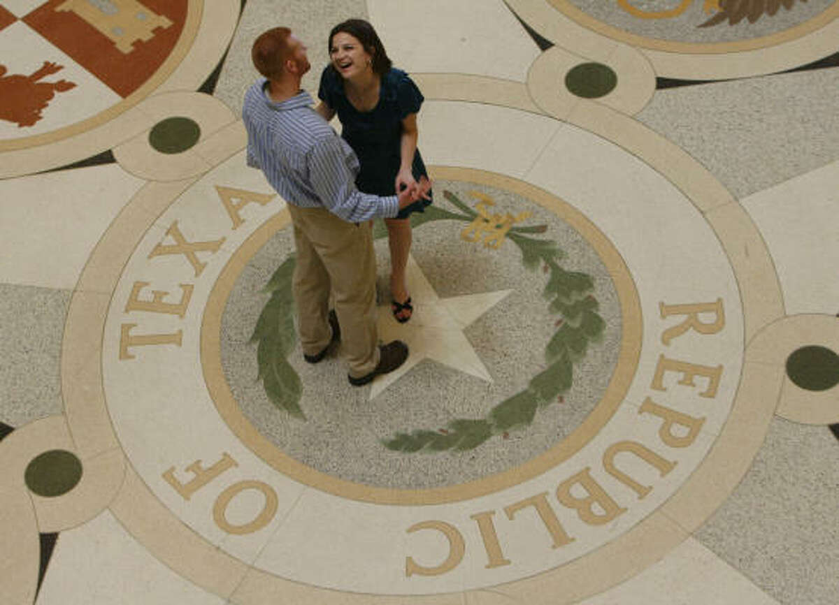 Courtney Morgan, 24, laughs with her fiance Randy Sharp, 28, as the couple posed for engagement photos inside the Texas State Capitol on Monday.