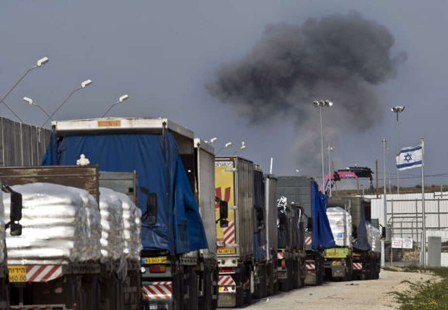 Jan. 13, 2008:A convoy of humanitarian aid awaits entry to the Gaza Strip at the Israeli side of the Rafah border crossing as smoke billows from the Palestinian enclave following an Israeli air strike. Israeli troops and Palestinian fighters fought fierce battles in the streets of Gaza City early Jan. 13 as a war on Hamas that has killed more than 900 Palestinians entered its 18th day. Photo: YOAV LEMMER, AFP/Getty Images