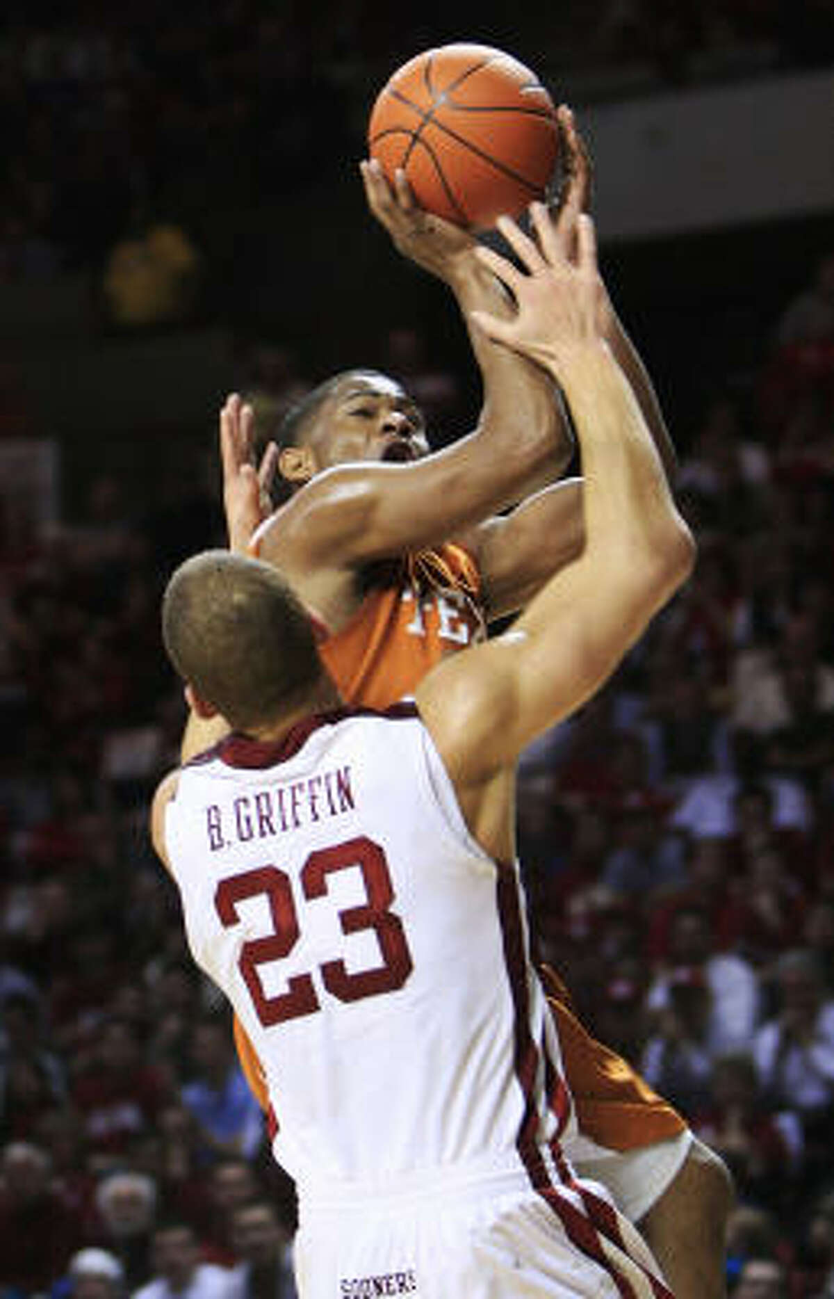 Texas guard Harrison Smith, rear, is called for an offensive foul as he runs into Oklahoma forward Blake Griffin on his way to the basket in the first half.