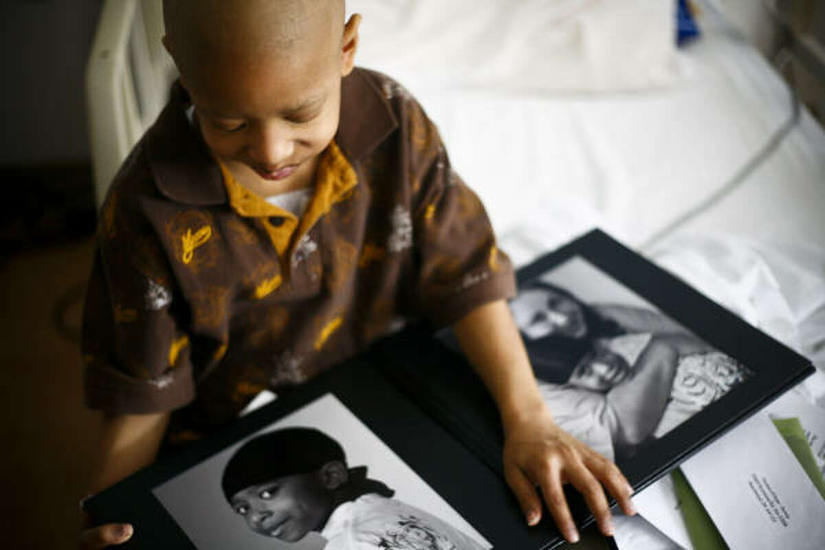Zereth Day, 6, looks at photos of himself and his mother taken by Flashes of Hope two months ago before a new photo shoot Jan. 9. Zereth suffers from leukemia.