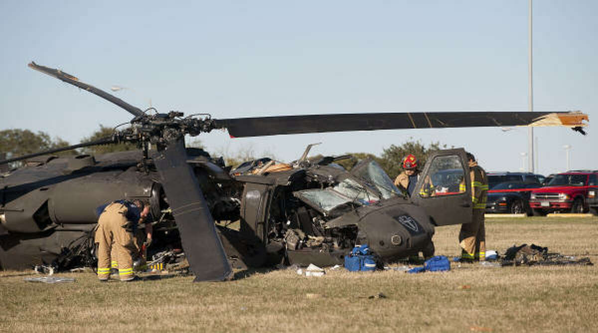 Emergency personnel work at the crash scene. Witnesses said they saw five Black Hawk helicopters taking off and landing throughout the day.