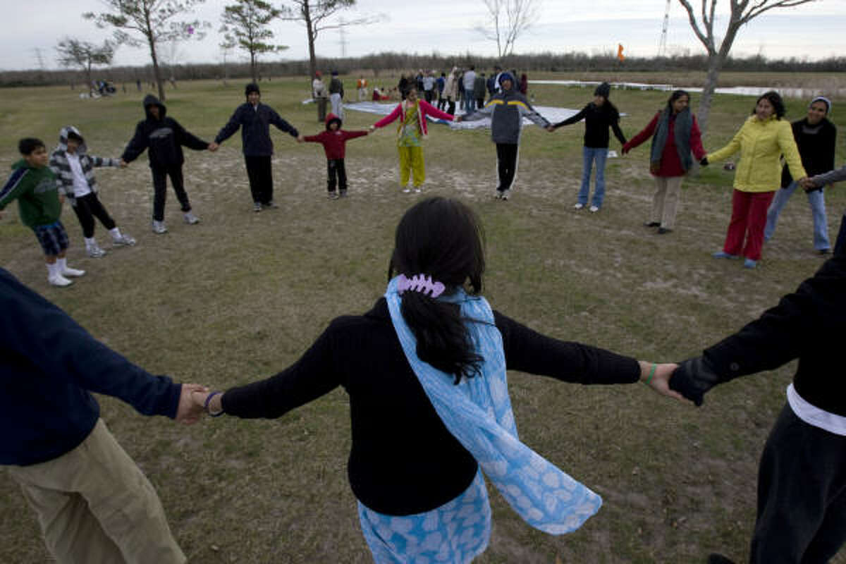 More than 20 Houston-area Hindus form a circle to play a game at George Bush Park Sunday.