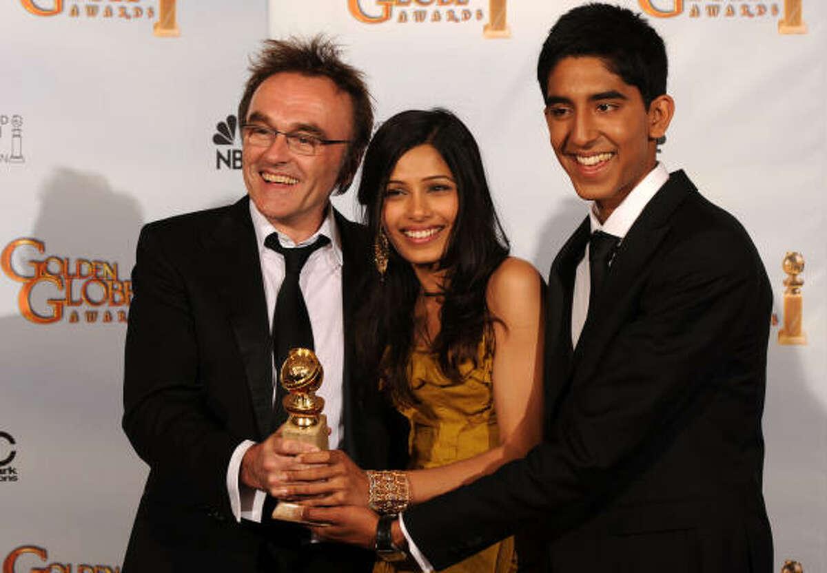 Los grandes ganadores de la noche, el director Danny Boyle (izq.) y los actores Freida Pinto (centro) y Dev Patel posan con el premio que ganaron por la mejor película, Slumdog Millionaire.