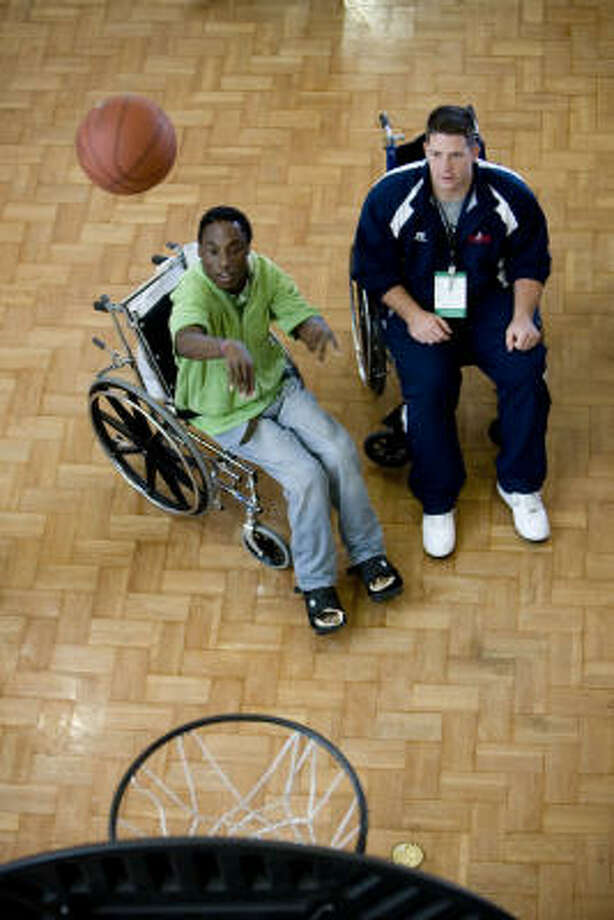 Isiah Jacobs, left, shoots for two with Cal long snapper Nick Sundberg, right, as star college athletes visited and played with Houston and Galveston Shrine Hospital patients at Shriners Hospital on Sunday. Photo: Eric Kayne, Chronicle