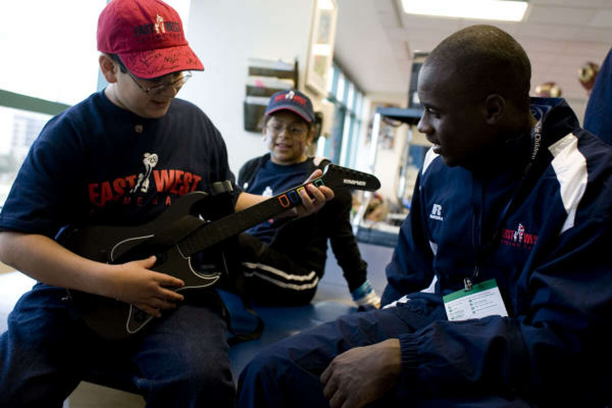 Miguel Garcia, 12, teaches Oregon State defensive back Brandon Hughes a Guitar Hero video game trick as sister Sabrinna, 11, looks on Sunday.
