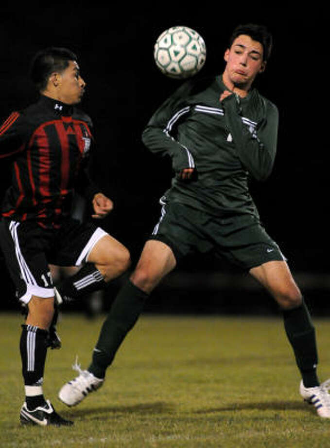The Woodlands senior defender Max Miller, right, goes one-on-one against Westfield senior forward Fredy Agueta. Photo: Jerry Baker, For The Chronicle