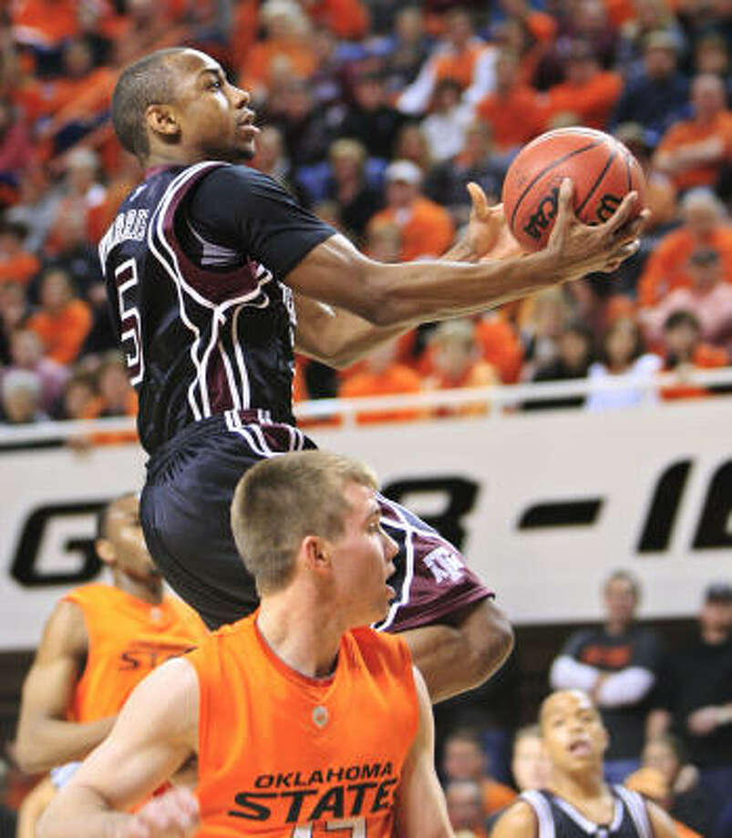 Oklahoma State 72, Texas A&M 61 Texas A&M guard Dash Harris, left, goes up for a shot behind Oklahoma State guard Kelton Page, right, in the first half. Photo: Sue Ogrocki, AP
