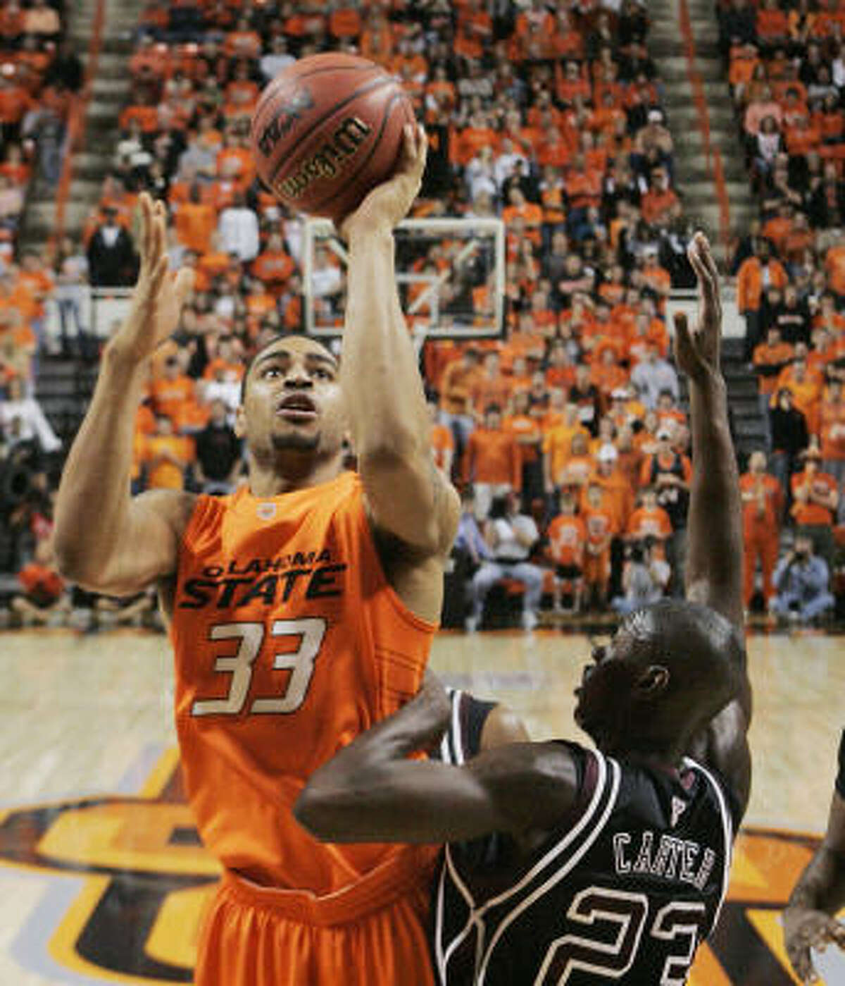 Oklahoma State 72, Texas A&M 61 Oklahoma State forward Marshall Moses, left, shoots over Texas A&M guard Josh Carter.