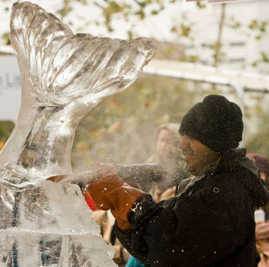 "Marco Antonio Villarreal, who calls himself the ""Vegas Iceman,"" works on a sculpture of a fish. Ice sculptors from around the country used chain saws, blow torches, dry ice and other tools to create sculptures in Discovery Green Saturday. Photo: Steve Campbell, Houston Chronicle"