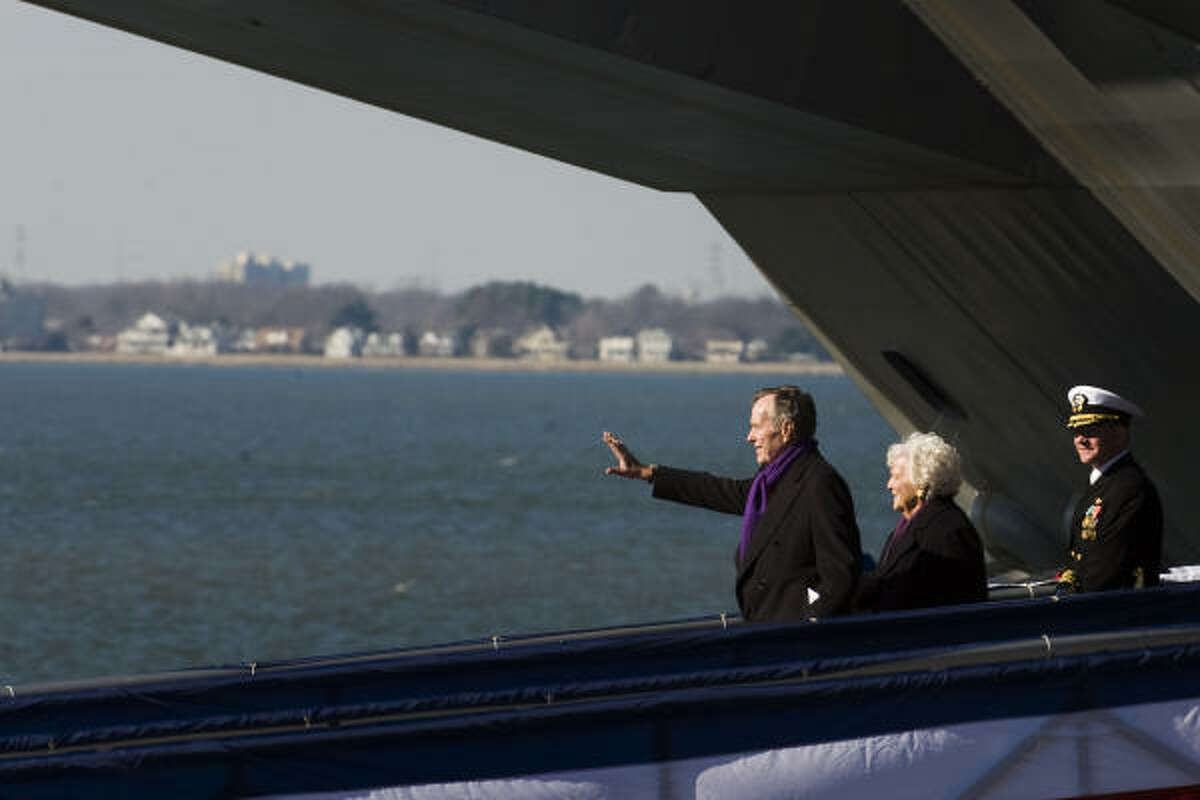 President George H.W. Bush waves to the crowd as he walks down the gangway with his wife Barbara following commissioning ceremonies for the USS George H.W. Bush aircraft carrier.
