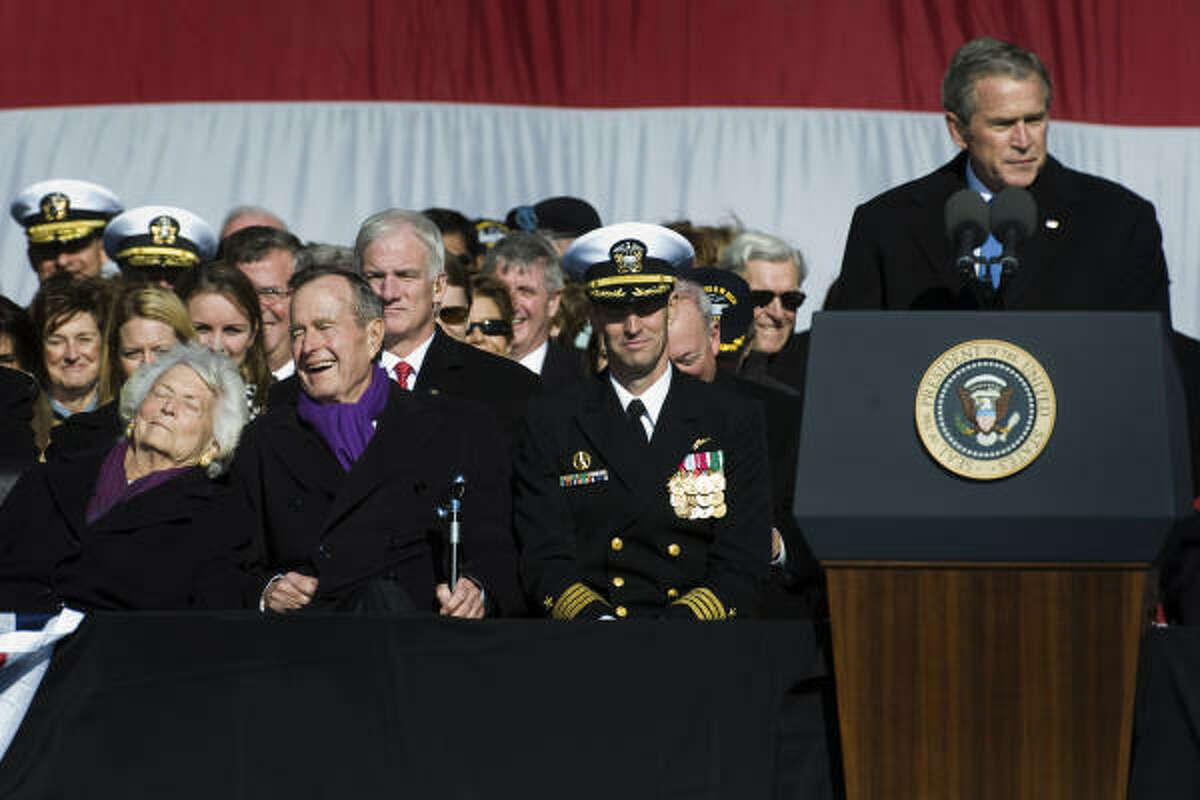 Former President George H.W. Bush laughs with his wife Barbara after a remark made by their son, President George W. Bush, as he addresses the commissioning ceremony. The younger Bush referred to his mother as a