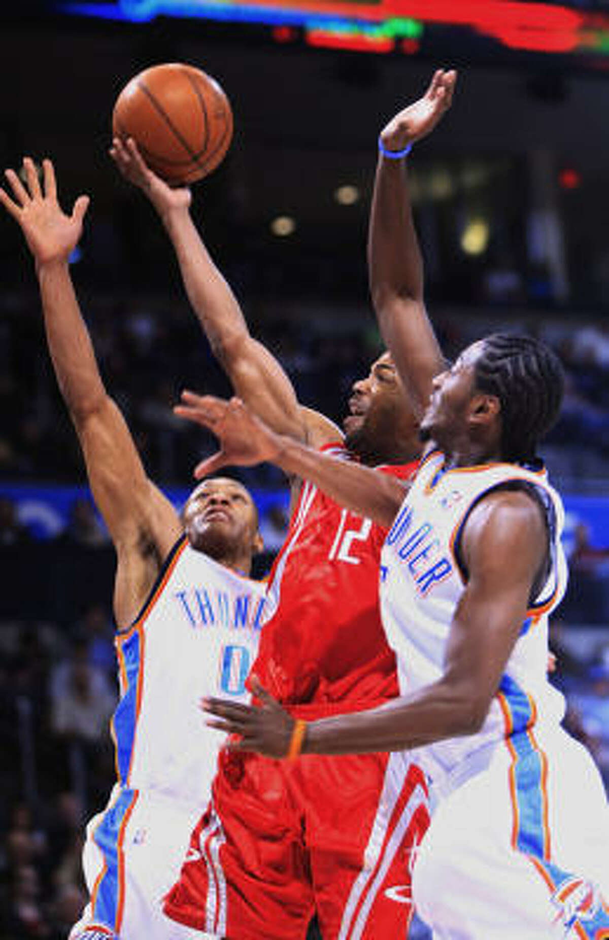 Rafer Alston, center, splits Thunder defenders Russell Westbrook, left, and guard Kyle Weaver on his way to the basket in the first quarter.