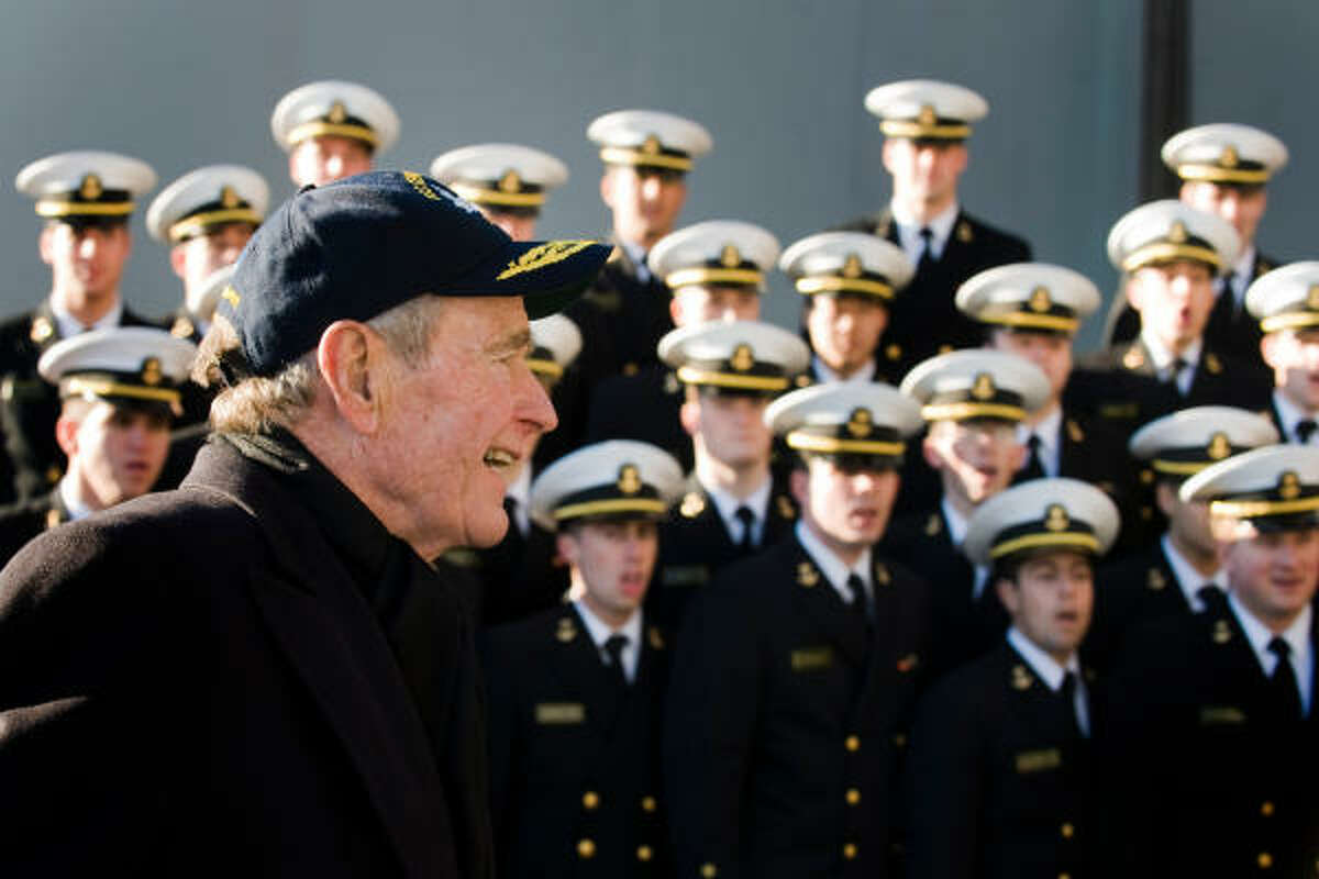 The former president is serenaded by a Navy choir as he steps onboard the USS George H.W. Bush.