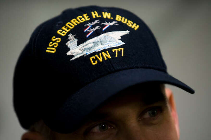 An officers hat shows the USS  George H.W. Bush and the ship's designation of CVN77.