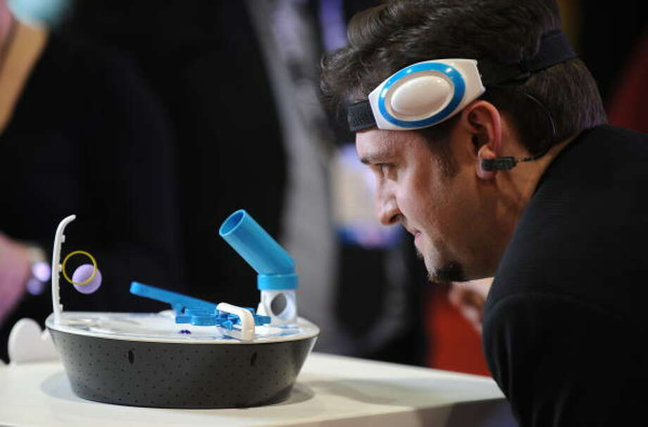 Tim Sheridan uses his mind to raise a small purple foam ball as he demonstrates the Mindflex game at the Mattel display at the 2009 Consumer Electronics Show in Las Vegas on Jan. 8. The game will be available in the fall at a projected retail price of $79.99. Photo: ROBYN BECK, AFP/Getty Images