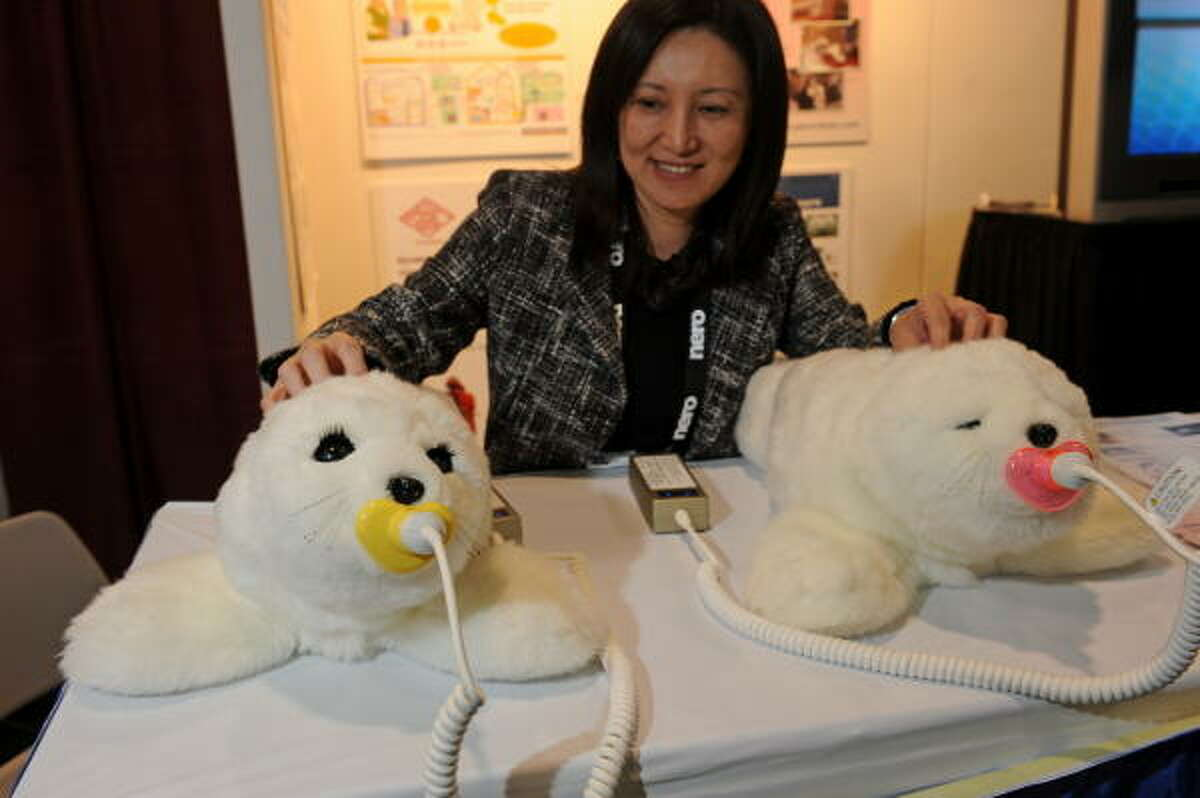 Christine Hsu pets two Paro therapeutic robots on display at the Japan External Trade Organization at the 2009 Consumer Electronics Show. Paro, responds to light, sound, temperature, touch, motion and temperature. Over time, Paro develops its own character. Paro can provide companionship to people not able to take care of a real animal, such as those in hospitals, elder care centers and nursing homes.