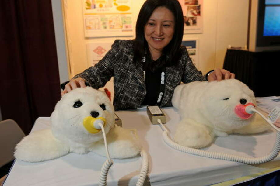 Christine Hsu pets two Paro therapeutic robots on display at the Japan External Trade Organization at the 2009 Consumer Electronics Show.  Paro, responds to light, sound, temperature, touch, motion and temperature.  Over time, Paro develops its own character. Paro can provide companionship to people not able to take care of a real animal, such as those in hospitals, elder care centers and nursing homes. Photo: ROBYN BECK, AFP/Getty Images