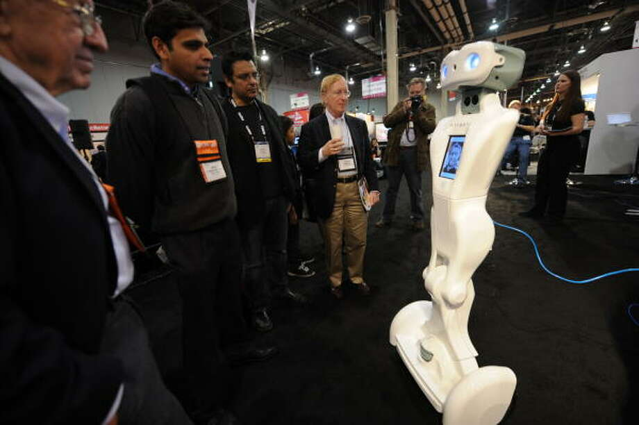 The QA telepresence robot by Anybots chats with people on the floor at the 2009 Consumer Electronics Show in Las Vegas Jan. 8.  The robot's user operates QA from an online laptop computer anywhere in the world, talking through a headset and controlling the robot's movement. Photo: ROBYN BECK, AFP/Getty Images