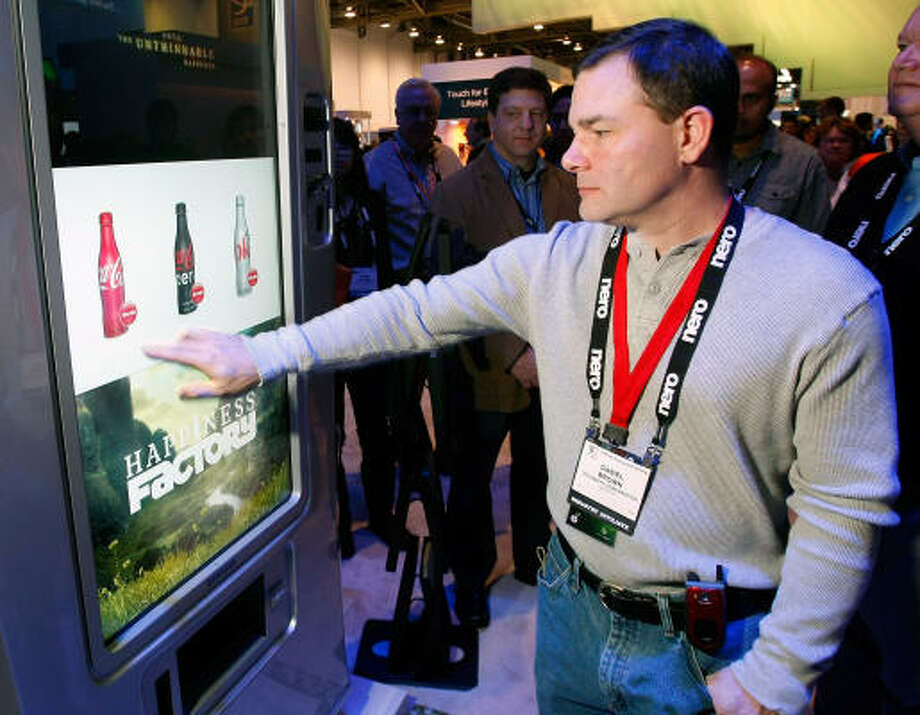 Daniel Brown gets a Coke at Samsung's new interactive uVend machine at the 2009 International Consumer Electronics Show at the Las Vegas Convention Center Jan. 9. Samsung, Sapient and Coca-Cola collaborated on the machines that feature touch screen displays, shock sensors and Wi-Fi and will be beta tested in malls in 2009. Photo: Ethan Miller, Getty Images