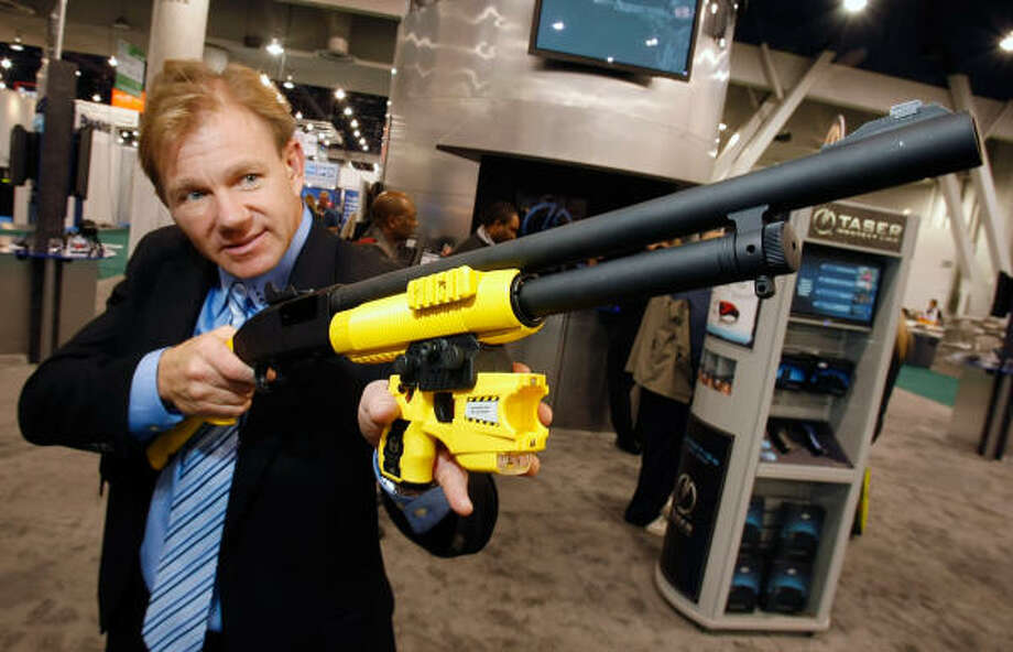 Taser International vice president of communications Steve Tuttle displays a Mossberg Less Lethal Shotgun that fires a Taser round in a shotgun shell at the 2009 International Consumer Electronics Show at the Las Vegas Convention Center Jan. 9. The shotgun fires what is called an extended range electronic projectile (XREP) 75-100 feet. The new system can work with any 12-gauge shotgun and will be available for law enforcement personnel in March 2009. Photo: Ethan Miller, Getty Images