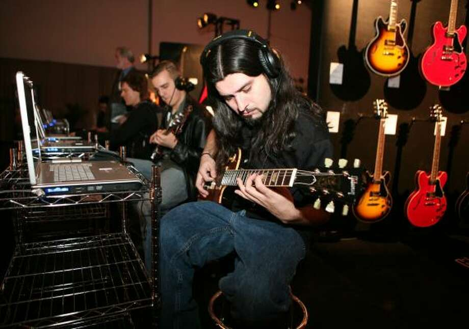 Gabriel Rocha, of Commerce, Calif., plays a Gibson electric guitar at an interactive display at the Gibson structure during the International Consumer Electronics Show Friday, Jan. 9. Photo: Ronda Churchill, AP